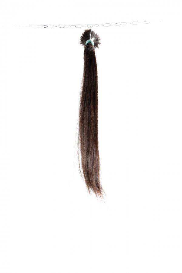 Tmavé vlasy v surovém copu.