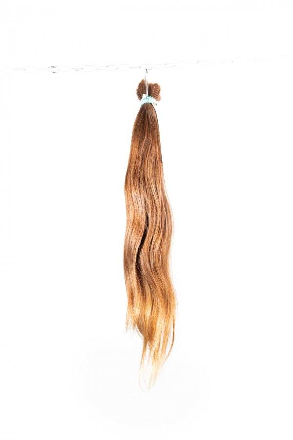 Světle hnědé vlasy s lehkou vlnou k prodlužování.