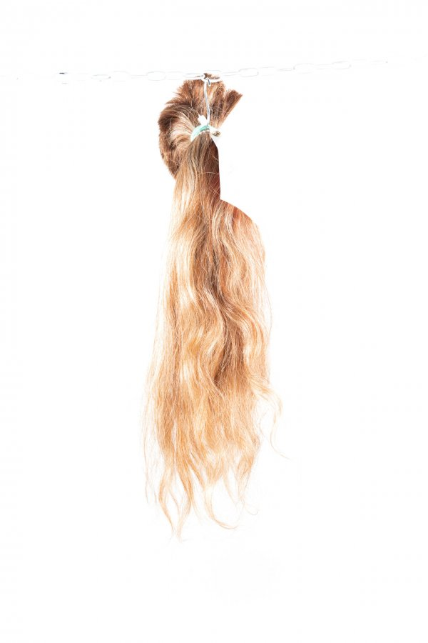 Světlé vlasy s lehkou vlnou.